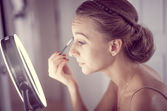 putting on makeup with mirror